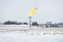 Drillers burn off the natural gas that surfaces with oil on a farm in North Dakota. Photo: Spencer Lowell/Bloomberg Markets